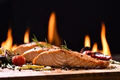 Poissons saumonés grillés et divers légumes images stock