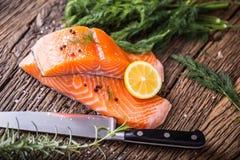 Poissons saumonés Romarin saumoné cru de citron d'aneth de sel de poivre de filet sur la table en bois Image libre de droits