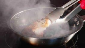 Poissons sautés, le filet de thon sur la poêle de cuisson à la vapeur dans le mouvement lent banque de vidéos