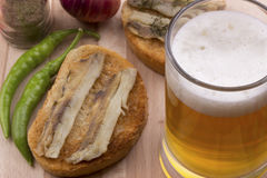 Poissons sur le pain grillé et la bière blonde image stock