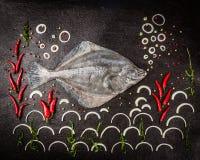 Poissons uniques entiers crus avec des épices, des algues et l'oignon sur le fond en pierre foncé photographie stock libre de droits