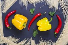 Poivre amer avec le poivre jaune sur un fond noir Pâtes avec le poivron rouge amer et le poivre jaune Esprit de poivrons jaunes e Images libres de droits