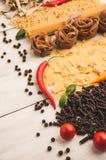 Poivre d'un rouge ardent amer avec différents genres de pâtes sur un fond en bois blanc Photographie stock libre de droits
