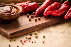 Poivre de piment et sauce rouge sur le conseil Image stock