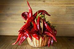 Poivre de piments d'un rouge ardent dans le panier sur le fond en bois de table Images stock