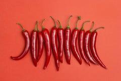 Poivre de piments rouges sur un fond rouge Photographie stock