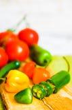 Poivre et tomates assortis sur le fond en bois photographie stock libre de droits