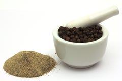Poivre finement moulu sous les grains de poivre entiers Image stock
