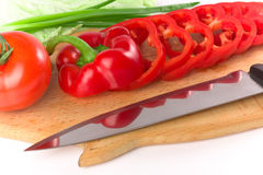 Poivre frais mûr rouge coupé en tranches sur le panneau de découpage Images libres de droits