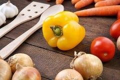Poivre jaune avec des légumes et des cuillères de cuisson Photos libres de droits
