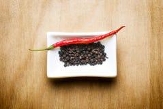Poivre noir de /poivron d'un rouge ardent sur la table en bois Image libre de droits