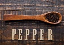 Poivre noir sur la cuillère en bois avec des lettres ci-dessous Photographie stock