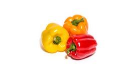Poivre rouge, orange et jaune d'isolement sur le blanc Image stock
