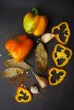 Poivron doux jaune - entier et coupé en tranches avec les épices et l'ail sur un fond gris photos stock
