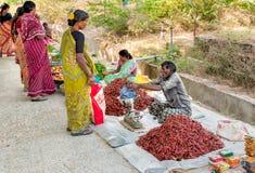 Poivron rouge de vente indienne d'homme au marché en plein air de Puttaparthi photographie stock libre de droits
