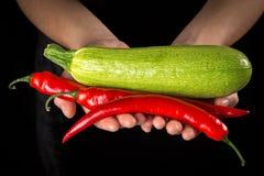 Poivron rouge et courgette verte chez des mains de la femme sur le fond noir photographie stock libre de droits