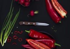 Poivron rouge frais sur la table noire Images stock