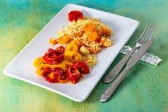 Poivron rouge jaune cuit au four et riz blanc cuit avec les carottes d?licieuses d'un plat en c?ramique blanc photo libre de droits