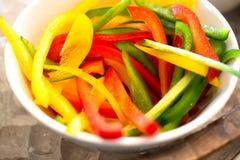 Poivrons colorés coupés en tranches dans la cuvette blanche Photo stock