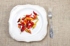 Poivrons de piment d'un rouge ardent du plat blanc. Images libres de droits