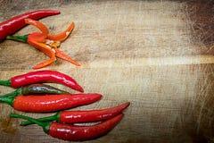 Poivrons de piment d'un rouge ardent frais sur le fond en bois rustique Image stock