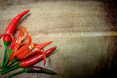 Poivrons de piment d'un rouge ardent frais sur le fond en bois rustique Photo stock