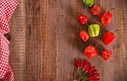 Poivrons de piment d'un rouge ardent sur la table en bois Photo libre de droits
