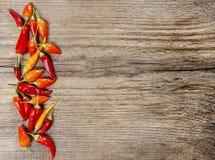 Poivrons de piment d'un rouge ardent sur le fond en bois Photos libres de droits