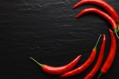 Poivrons de piment d'un rouge ardent sur un fond foncé Image stock
