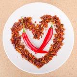 Poivrons de piment fort disposés dans la forme de coeur Photo stock