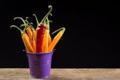 Poivrons de piment jaune et rouge dans un seau coloré Photos stock