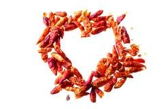 Poivrons de piment rouge secs dans une forme de coeur d'isolement sur un CCB blanc Images libres de droits