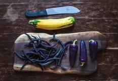Poivrons de piment violets, haricots et courgette jaune dessus Images libres de droits