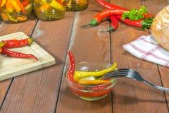 Poivrons de piments marinés conservés dans le bol en verre avec la fourchette, fraîche Photo libre de droits