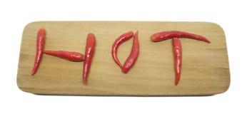 Poivrons de piments thaïlandais d'un rouge ardent dans un mot chaud sur une planche à découper Photos stock