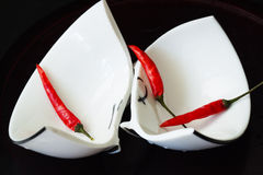 Poivrons de tasse blanche cassée et de piment rouge Image libre de droits