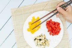 Poivrons doux et aubergine coupés en tranches du plat blanc Mains de femelle tenant des bâtons de nourriture Concept est de cuisi Photos libres de droits