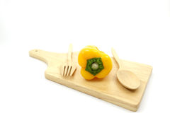 Poivrons doux jaunes de plat en bois avec la cuillère en bois et la fourchette en bois Photographie stock