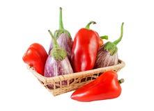 Poivrons et aubergines dans le panier d'isolement sur le blanc Photographie stock