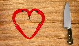 Poivrons et couteau de piment d'un rouge ardent sur couper le conseil en bois Photo libre de droits