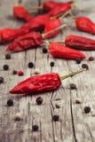 Poivrons et poivre de Jamaïque de piment rouge secs sur un bois Photos stock
