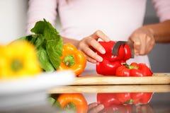 Poivrons - femme coupant le poivron rouge Image stock