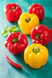 Poivrons jaunes rouges végétaux sains sur le fond de turquoise Photographie stock