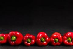 Poivrons rouges dans la ligne sur le fond noir avec l'espace de copie - photo de plan rapproché des légumes doux mûrs frais entie image stock