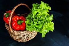 Poivrons rouges et groupe mûrs de salade verte dans le panier en osier sur le fond foncé photo stock