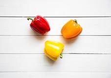 Poivrons rouges, oranges et jaunes sur la table en bois blanche Photographie stock libre de droits
