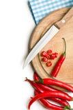 Poivrons rouges sur la planche à découper Photos stock