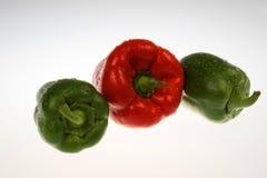 Poivrons verts et rouges avec des gouttes de l'eau d'isolement sur le blanc Image stock