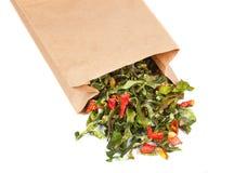 Poivrons verts secs dans le sac de papier d'isolement sur le fond blanc Photographie stock