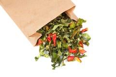 Poivrons verts secs dans le sac de papier d'isolement sur le fond blanc Photo libre de droits